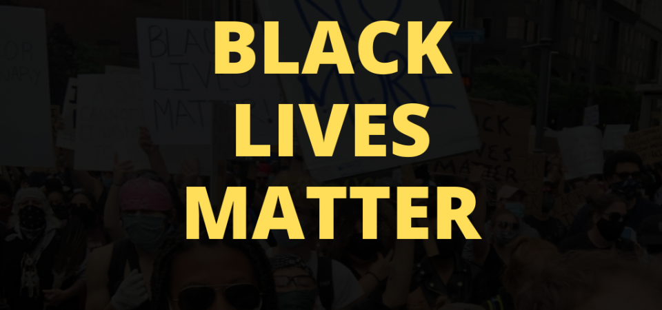 """Yellow Text Reads """"Black Lives Matter"""" Over a Black Background with Vague Image of Protest"""