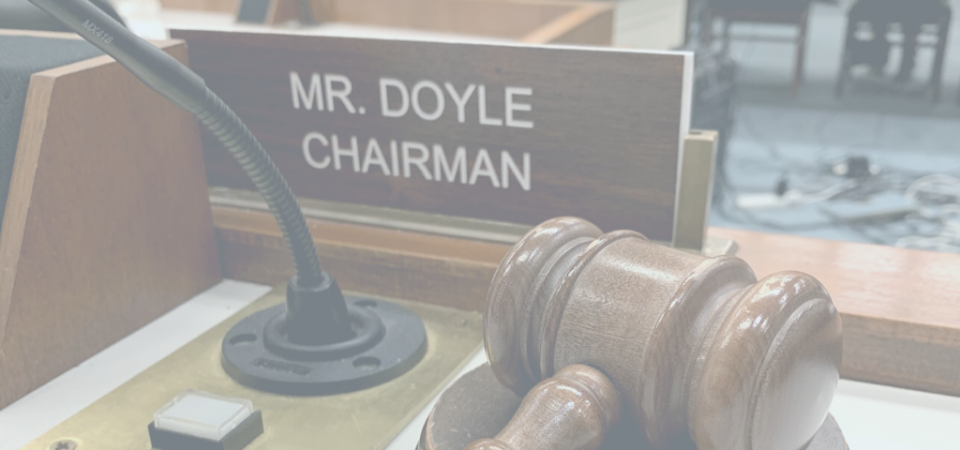 "Plaque that reads, ""Mr Doyle Chairman"" next to a wooden gavel on a podium"